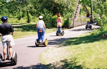 Picture of a line of people going down a path on Segways
